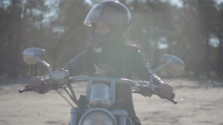runaway : Portrait cute girl wearing black helmet sitting on the motorcycle looking away. Hobby, traveling and active lifestyle. Biker on her motorbike outdoors. Leisure and travel by motorcycle. Soft light. Stock Footage
