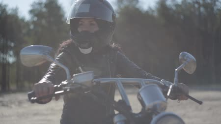 runaway : Portrait cute woman wearing black helmet sitting on the motorcycle looking away. Hobby, traveling and active lifestyle. Biker on her motorbike outdoors. Leisure and travel by motorcycle. Soft light. Stock Footage