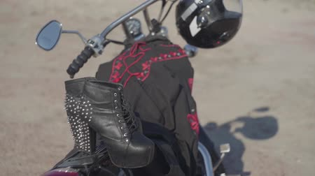highheels : Spiked shoes with high heels and black and red dress lying on the motorcycle close-up. The motorbike with the helmet on the wheel on the riverbank. Hobby, traveling and active lifestyle