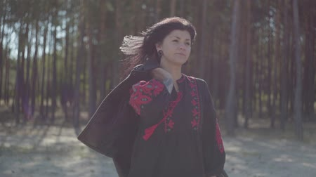 bizakodó : Attractive caucasian young woman in beautiful long black and red dress standing in the pine forest. Connection with nature. Slow motion.