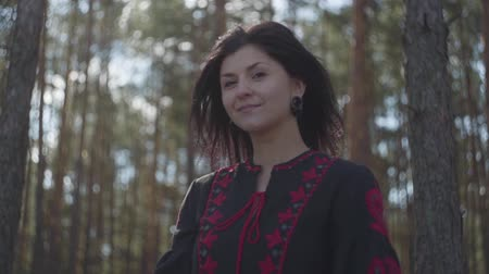 tur : Cute caucasian young woman in black and red dress standing in the pine forest looking to camera. Connection with nature. Slow motion.