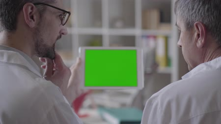 informal : Two experienced male doctors checking information on the tablet, discussing. Concept of medicine, health care and people, hospital. New modern fully functional medical facility. Green screen.