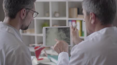 hastane : Two experienced male doctors checking x-ray of the lungs on the tablet, discussing. Concept of medicine, health care and people, hospital. New modern fully functional medical facility.