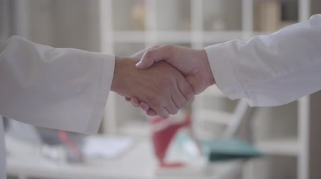 зарабатывать : Confident friendly handshake of two unrecognized male hands in white coats like doctors. Concept of medicine, health care and people, hospital. New modern fully functional medical facility.