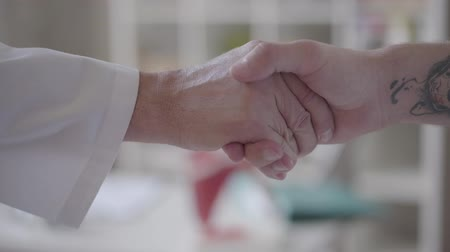 gyógyászati : Confident friendly handshake of two unrecognized male hands, one in white coats like doctors other like a patient. Concept of medicine, health care and people, hospital.