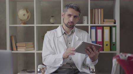 skillful : Portrait of handsome thoughtful man in white robe looking in the camera showing tablet with picture of x-ray of lungs. Skillful doctor in modern private clinic. New fully functional medical facility.
