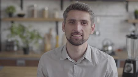spent : Portrait of a handsome bearded guy confidently looking at camera enjoying executive lifestyle on the background of a modern kitchen. Real people series Stock Footage