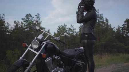 runaway : Skill caucasian woman in a black leather jacket and helmet riding a classic motorcycle. Girl removes the helmet standing near motorbike on the side of the road. Hobby, traveling and active lifestyle.