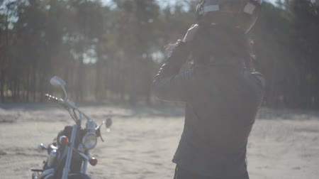 runaway : Cute caucasian woman wearing black leather jacket puts on helmet standing near classic motorcycle. Hobby, traveling and active lifestyle. Sunny weather, soft light. Slow motion. Stock Footage