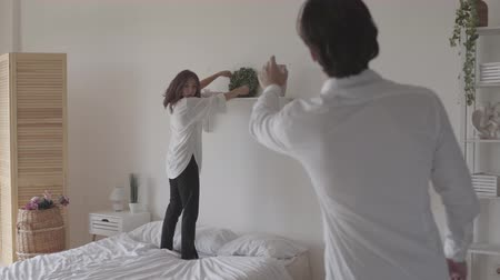 foto : Happy couple decorating the room together. Young woman putting the mural in the middle of the shelf while her husband directing her. Leisure of loving family
