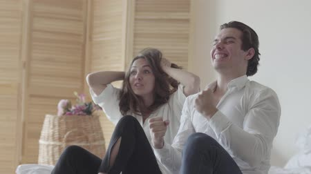 final : Emotional young man and woman watching soccer or baseball sitting on the bed. The relationship between man and woman. Football lovers at home together celebrate a goal Stock Footage