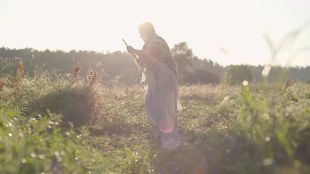 mow : Pretty overweight woman mowing the grass with the scythe on the green summer field. Folklore, traditions. Work in the field. Female farmer working on sunrise background at his farm. Real rural woman. Stock Footage