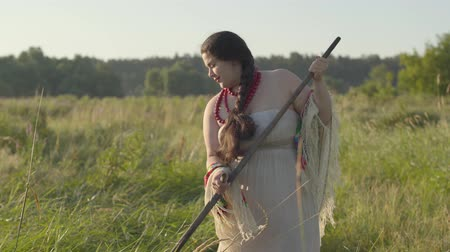 фольклор : Cute overweight woman mowing the grass with the scythe on the green summer field. Folklore, traditions. Work in the field. Female farmer working on sunrise background at his farm. Real rural woman. Стоковые видеозаписи