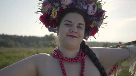 braids : Close-up portrait of beautiful overweight woman with a wreath on her head looking at the camera smiling in sunlight on the green summer field. Connection with nature. Real rural woman. Stock Footage