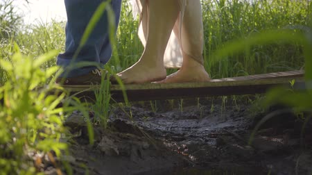 boso : Feet of man and woman cant miss each other on the wooden bridge close-up. Girl walking barefoot. Country lifestyle. Rural life, flirt concept