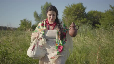круглолицый : Beautiful overweight woman walking in wild high grass with the earthen jar in the green summer field. Beautiful landscape. Traditions concept, connection with nature. Country lifestyle