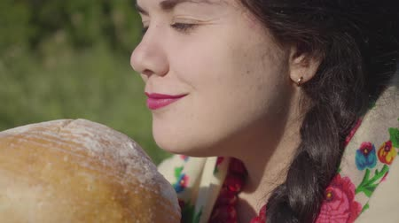 cheirando : Portrait of pretty plump woman sitting in grass sniffing tasty bread preparing to eat. Traditions concept, connection with nature. Country lifestyle. Real rural woman. Lunch break in the countryside. Stock Footage