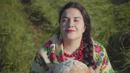 cheirando : Portrait of cute overweight woman sitting in grass sniffing tasty bread preparing to eat. Traditions concept. Country lifestyle. Real rural woman. Lunch break in the countryside.