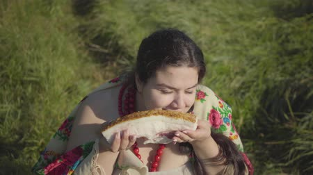 smalec : Portrait of beautiful overweight woman sitting in grass sniffing tasty lard preparing to eat. Traditions concept. Country lifestyle. Real rural woman. Lunch break in the countryside. Wideo