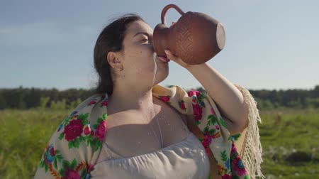 mow : Cute overweight woman enjoys drinking fresh milk from the earthen jug on the green summer field. Beautiful landscape. Folklore, traditions concept. Real rural woman. Stock Footage