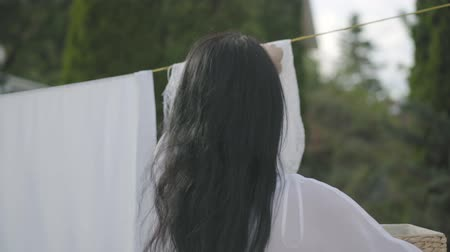 prendedor de roupa : Back view of attractive woman with long hair hanging white clothes on a clothesline outdoors. Washday. Girl doing laundry. Concept of sustainability, nature and purity and deep clean after washing. Stock Footage