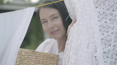 öltözet : Attractive mature woman with long hair and wicker basket in hands hanging white clothes on a clothesline outdoors and looking at camera smiling. Washday. Lady doing laundry Stock mozgókép