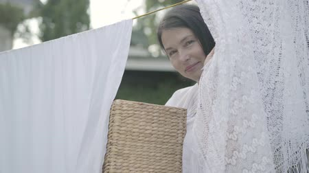 prendedor de roupa : Attractive mature woman with long hair and wicker basket in hands hanging white clothes on a clothesline outdoors and looking at camera smiling. Washday. Lady doing laundry Stock Footage