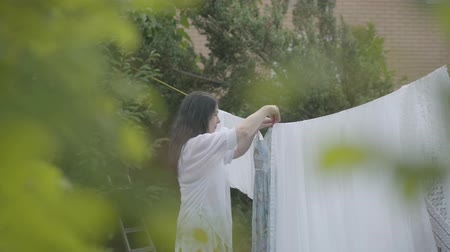 ruhacsipesz : Back view of attractive woman with long hair hanging white clothes on a clothesline outdoors. Washday. Girl doing laundry. Concept of sustainability.