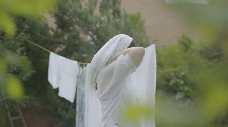 ruhacsipesz : Attractive mature woman with long hair removing white clean shawl from the clothesline, tying it to the head and looking at camera. Washday. Lady doing laundry Stock mozgókép