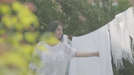 lavanderia : Cute mature woman with long hair hanging white clothes on a clothesline outdoors. Adult woman tying shawl to the head and looking at the camera. Washday. Lady doing laundry. Concept of sustainability, nature and purity and deep clean after washing. Stock Footage