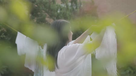 prendedor de roupa : Cute mature woman with long hair hanging white clothes on a clothesline outdoors. Adult woman tying shawl to the head and looking at the camera. Washday. Lady doing laundry. Concept of sustainability, nature and purity and deep clean after washing. Stock Footage