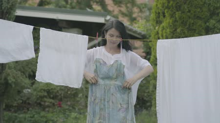 prendedor de roupa : Attractive mature woman with long hair hanging her clothes on a clothesline outdoors, then trying on the dress and looking at camera smiling. Washday. Lady doing laundry Stock Footage