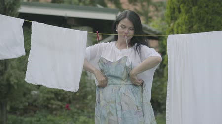 prendedor de roupa : Cute mature woman with long hair hanging her clothes on a clothesline outdoors, then trying on the dress and looking at camera smiling. Washday. Lady doing laundry Stock Footage
