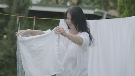prendedor de roupa : Attractive senior woman with long hair black hair hanging white clothes on a clothesline outdoors. Washday. Positive housewife doing laundry Stock Footage