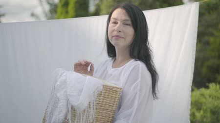 varal : Adorable mature woman with long black hair holding wicker basket in hands while hanging white clothes on a clothesline outdoors and looking at camera. Washday. Senior woman doing laundry.