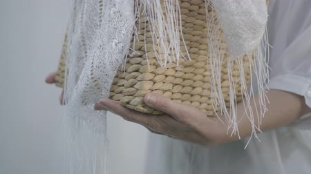 varal : Close-up hands of mature woman holding wicker basket while hanging white clothes on a clothesline outdoors. Washday. Housewife doing laundry