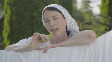 ruhacsipesz : Attractive senior woman with shawl on her head eating green pepper looking at camera smiling over the clothesline outdoors. Washday. Pretty housewife doing laundry.