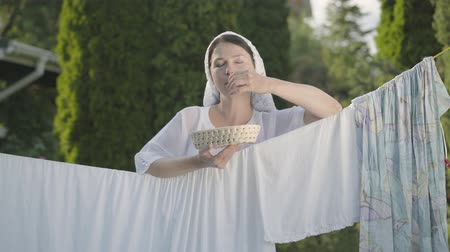 prendedor de roupa : Pretty woman with white shawl on her head eating cherries looking at camera smiling over the clothesline outdoors. Washday. Positive housewife doing laundry