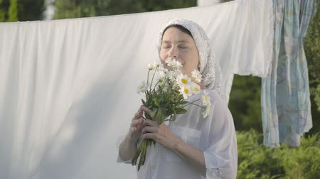 cheirando : Attractive senior woman with white shawl on her head sniffing daisies looking at camera smiling at the clothesline outdoors. Washday. Positive carefree housewife doing laundry Stock Footage