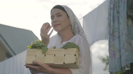 varal : Portrait senior woman with a white shawl on her head holding the basket with vegetables sniffing cherry tomato near the clothesline outdoors. Positive housewife doing homework