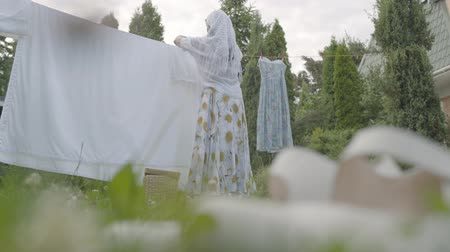 prendedor de roupa : Mature housewife woman hanging just washed clean laundry on clothesline outside her house in a sunny day. Concept of sustainability, nature and purity and deep clean after washing. Stock Footage