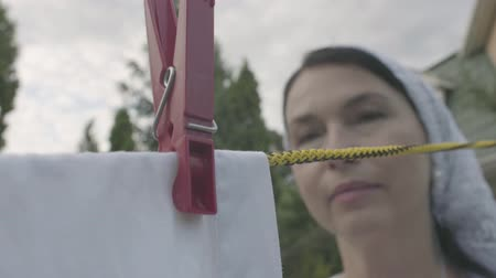 prendedor de roupa : Attractive senior woman with a white shawl on her head hanging white clothes on a clothesline using clothespin outdoors close-up. Washday. Lady doing laundry Stock Footage
