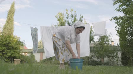 domácí práce : Attractive senior woman with a white shawl on her head hanging bed linen on the rope in the garden close-up. Washday. Positive housewife doing laundry.