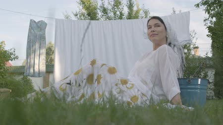 szárítókötél : Attractive senior woman with a white shawl on her head resting in the garden sitting on the grass in front of the clothesline. Washday. Positive housewife resting after doing laundry. Bottom view