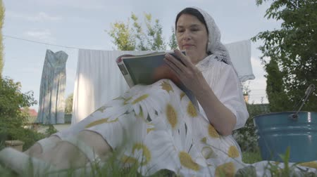 ruhacsipesz : Attractive senior woman with a white shawl on her head resting in the garden sitting on the grass in front of clothesline reading magazine. Positive housewife resting after doing laundry. Bottom view