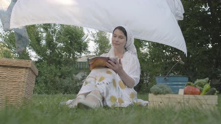 ruhacsipesz : Adorable woman with a white shawl on her head resting in the garden sitting on the grass in front of clothesline reading magazine. Positive housewife resting after doing laundry. Bottom view