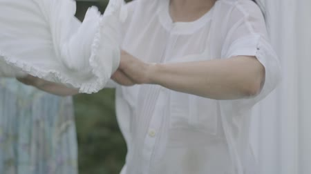 clothesline : Unrecognized mature woman holding wicker basket while hanging white clothes on a clothesline outdoors. Washday. Housewife doing laundry. Slow motion.