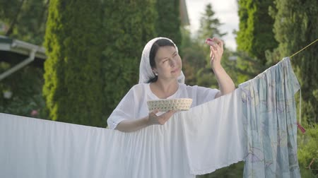 szárítókötél : Pretty woman with white shawl on her head eating cherries looking at camera smiling over the clothesline outdoors. Washday. Positive housewife doing laundry. Slow motion.