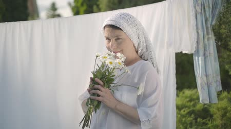 ruhacsipesz : Cute mature woman with white shawl on her head tears off daisy petals at the clothesline outdoors. Washday. Positive carefree housewife doing laundry. Shooting from behind tree brunch. Slow motion.