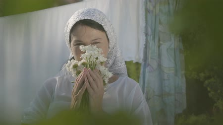 ruhacsipesz : Adorable woman with white shawl on her head sniffing daisies looking at camera near the clothesline outdoors. Washday. Positive carefree housewife doing laundry